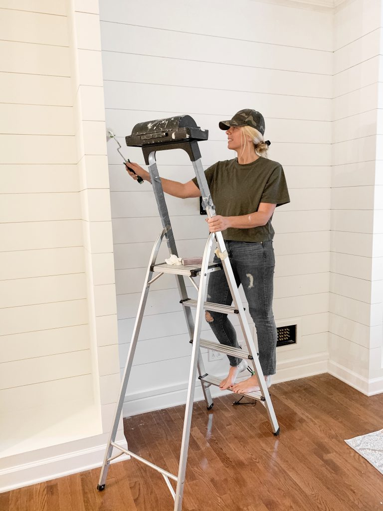 girl standing on ladder painting shiplap on media cabinet