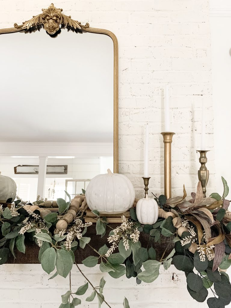 gold mirror and gold candlesticks on mantel