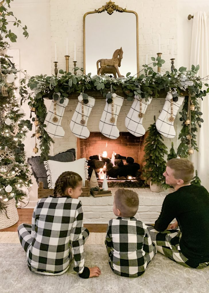 three children in buffalo plaid pajamas sitting by the fire