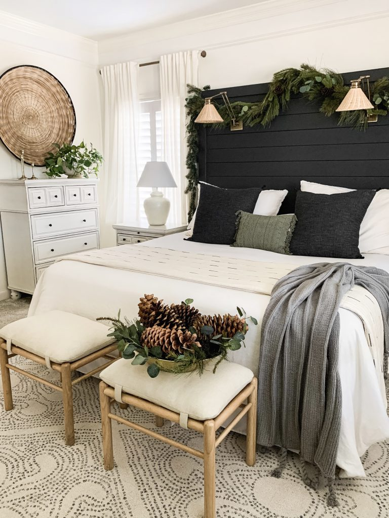ottomans with gold bowl of pine cones at the foot of the bed