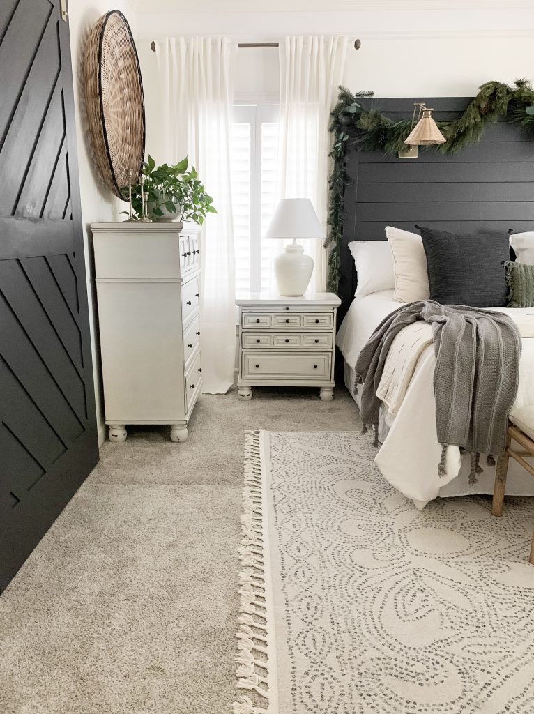 side view of nightstand beside bed with white lamp
