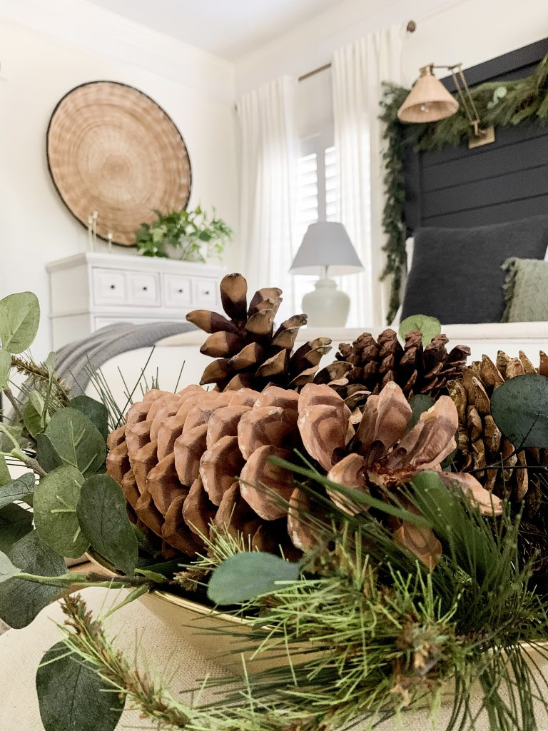 close up shot of the pine cones and greenery in gold bowl