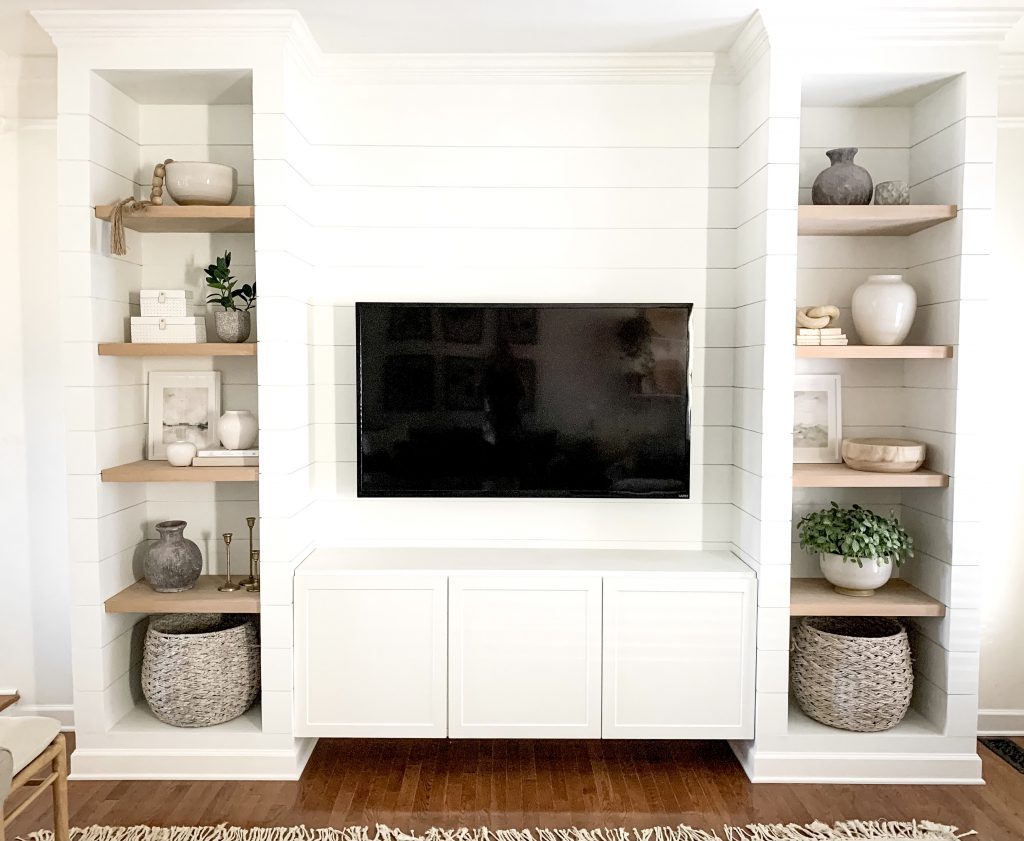 large white shiplapped media cabinet with shelves on either side of tv