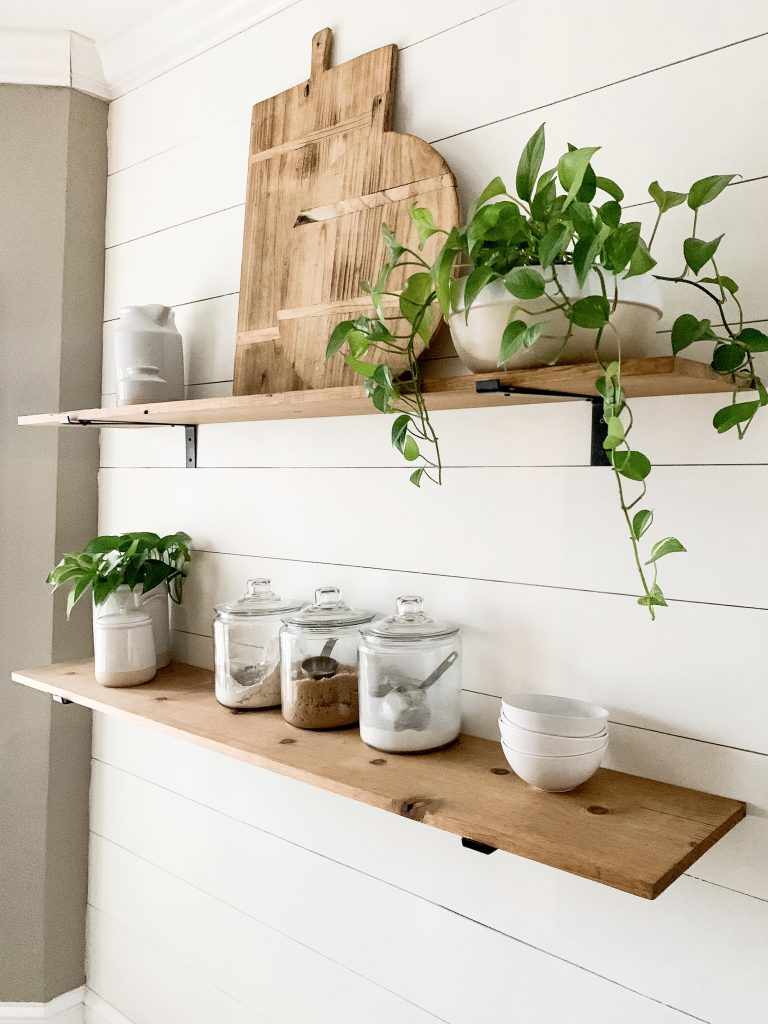 plants and cutting board decor on open shelves in kitchen