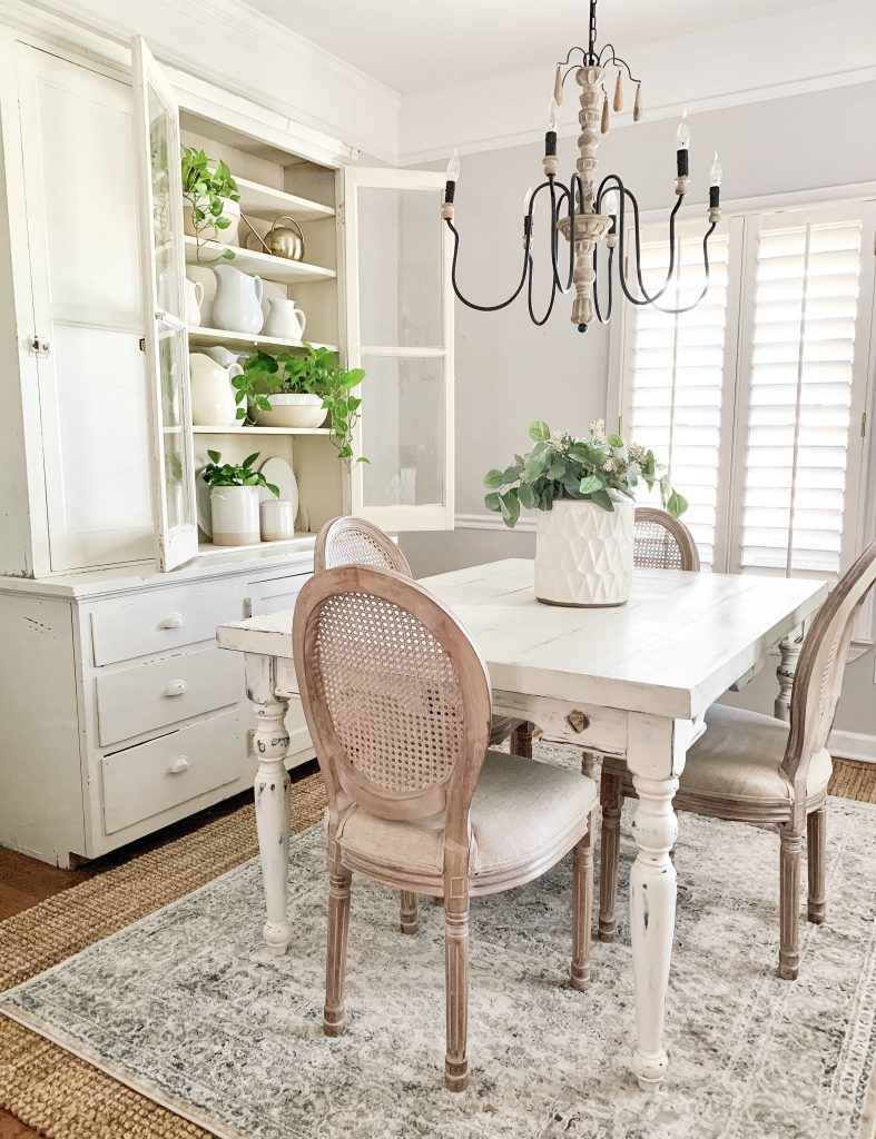 dining room with hutch, dining table, and cane back chairs